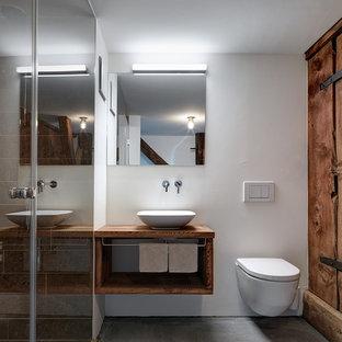 Immagine di una stanza da bagno con doccia rustica di medie dimensioni con nessun'anta, ante in legno scuro, WC sospeso, pareti bianche, pavimento in cemento, lavabo a bacinella, top in legno, pavimento grigio e top marrone