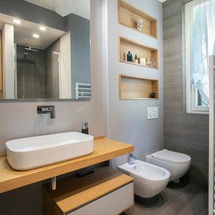 Idee per una stanza da bagno con doccia minimal di medie dimensioni con pavimento grigio, nessun'anta, ante grigie, doccia aperta, WC a due pezzi, piastrelle grigie, pareti grigie, parquet chiaro, lavabo a bacinella, top in legno, porta doccia a battente e top beige