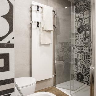 Ispirazione per una stanza da bagno con doccia design di medie dimensioni con doccia a filo pavimento, WC monopezzo, piastrelle di cemento, pareti grigie, pavimento in legno massello medio, pavimento marrone e porta doccia a battente