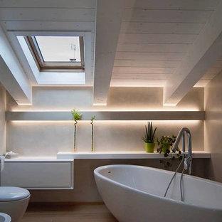 Foto di una stanza da bagno minimal con vasca freestanding, WC sospeso, pareti beige, parquet chiaro e pavimento beige