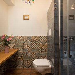 Immagine di una stanza da bagno con doccia design di medie dimensioni con doccia alcova, WC sospeso, piastrelle multicolore, piastrelle a mosaico, pareti bianche, pavimento in terracotta, pavimento marrone, porta doccia a battente, top beige e mobile bagno sospeso