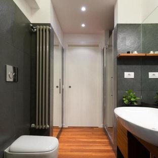 Ispirazione per una stanza da bagno con doccia design di medie dimensioni con ante lisce, ante in legno scuro, doccia alcova, WC sospeso, piastrelle grigie, pareti bianche, lavabo a bacinella, pavimento marrone, porta doccia a battente, top nero, un lavabo e mobile bagno incassato