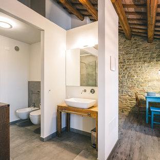 Idee per una stanza da bagno country di medie dimensioni con consolle stile comò, ante in legno scuro, pareti bianche, lavabo a bacinella, top in legno, pavimento grigio e top marrone