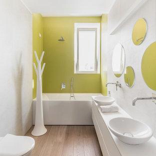 Exempel på ett mellanstort modernt en-suite badrum, med släta luckor, vita skåp, ett badkar i en alkov, en dusch/badkar-kombination, en vägghängd toalettstol, gröna väggar, mellanmörkt trägolv, ett fristående handfat, brunt golv och med dusch som är öppen