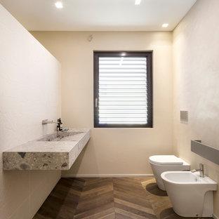 Inredning av ett modernt grå grått badrum, med ett urinoar, beige väggar, mellanmörkt trägolv, ett integrerad handfat och brunt golv