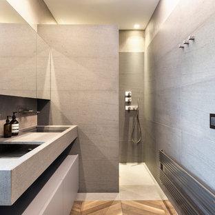 Immagine di una stanza da bagno con doccia contemporanea con ante grigie, piastrelle grigie, lavabo integrato, top grigio, zona vasca/doccia separata, pavimento grigio e doccia aperta