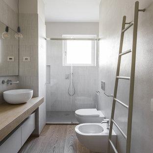 Inredning av ett modernt mellanstort beige beige badrum med dusch, med släta luckor, vita skåp, en dusch i en alkov, en bidé, ett fristående handfat, träbänkskiva, dusch med gångjärnsdörr, vit kakel och ljust trägolv