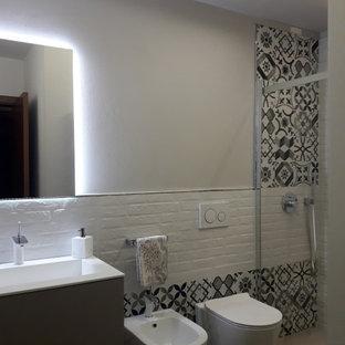 Пример оригинального дизайна: маленькая ванная комната в современном стиле с плоскими фасадами, серыми фасадами, душем без бортиков, инсталляцией, черно-белой плиткой, керамической плиткой, серыми стенами, полом из керамической плитки, душевой кабиной, монолитной раковиной, душем с раздвижными дверями, белой столешницей, тумбой под одну раковину, подвесной тумбой и многоуровневым потолком
