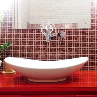Modelo de cuarto de baño principal, ecléctico, de tamaño medio, con armarios con paneles lisos, puertas de armario rojas, bañera esquinera, sanitario de pared, baldosas y/o azulejos beige, azulejos en listel, paredes blancas, suelo de baldosas de porcelana, lavabo sobreencimera, encimera de acrílico, suelo beige y encimeras rojas