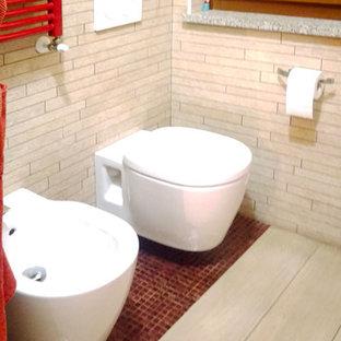 Imagen de cuarto de baño principal, ecléctico, de tamaño medio, con armarios con paneles lisos, puertas de armario rojas, bañera esquinera, sanitario de pared, baldosas y/o azulejos beige, azulejos en listel, paredes blancas, suelo de baldosas de porcelana, lavabo sobreencimera, encimera de acrílico, suelo beige y encimeras rojas