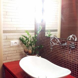 Foto de cuarto de baño principal, bohemio, de tamaño medio, con armarios con paneles lisos, puertas de armario rojas, bañera esquinera, sanitario de pared, baldosas y/o azulejos beige, azulejos en listel, paredes blancas, suelo de baldosas de porcelana, lavabo sobreencimera, encimera de acrílico, suelo beige y encimeras rojas