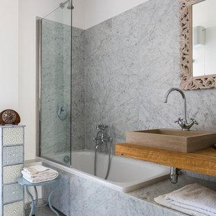 Immagine di una stanza da bagno design con vasca da incasso, vasca/doccia, piastrelle grigie, pareti bianche, lavabo a bacinella e doccia aperta