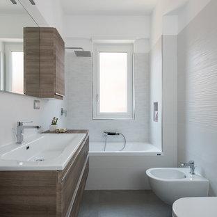 Foto di una stanza da bagno design con ante in legno bruno, vasca da incasso, vasca/doccia, WC a due pezzi, lavabo da incasso e pavimento grigio