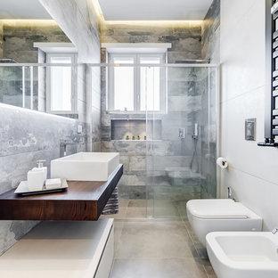 Immagine di una stanza da bagno con doccia contemporanea con nessun'anta, doccia alcova, WC sospeso, lavabo a bacinella, top in legno, pavimento grigio, porta doccia scorrevole e top marrone