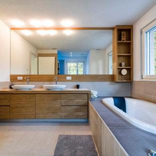 Esempio di una stanza da bagno design con lavabo a bacinella, ante lisce, ante in legno scuro, vasca da incasso e pareti bianche