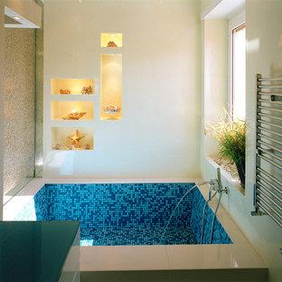 Imagen de cuarto de baño actual, de tamaño medio, con suelo de baldosas tipo guijarro, paredes blancas, suelo vinílico, suelo turquesa, armarios con paneles lisos, puertas de armario turquesas, bañera empotrada, sanitario de dos piezas, lavabo integrado y encimera de vidrio
