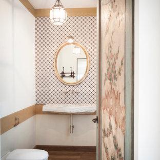 Foto di una stanza da bagno tradizionale di medie dimensioni con WC sospeso, piastrelle beige, piastrelle bianche, pareti multicolore, parquet scuro, lavabo sospeso e pavimento marrone