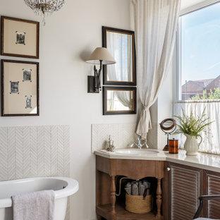 Неиссякаемый источник вдохновения для домашнего уюта: главная ванная комната среднего размера в классическом стиле с фасадами с филенкой типа жалюзи, коричневыми фасадами, ванной на ножках, душем без бортиков, раздельным унитазом, бежевой плиткой, удлиненной плиткой, бежевыми стенами, полом из керамогранита, накладной раковиной, столешницей из искусственного кварца, разноцветным полом, душем с раздвижными дверями и бежевой столешницей