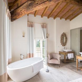 Immagine di una stanza da bagno padronale country con nessun'anta, ante in legno chiaro, vasca freestanding, pareti bianche, lavabo a bacinella e top in legno