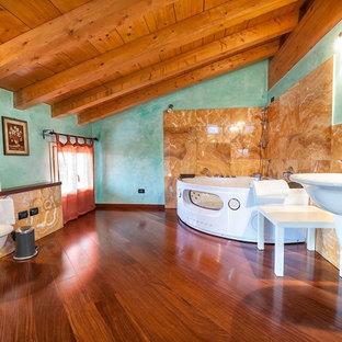 Immagine di una grande stanza da bagno padronale country con vasca idromassaggio, WC a due pezzi, piastrelle arancioni, piastrelle beige, piastrelle marroni, piastrelle di marmo, pareti blu, pavimento in legno massello medio, lavabo sospeso e pavimento marrone