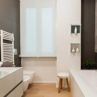 Foto di una stanza da bagno design con ante lisce, ante bianche, vasca sottopiano, vasca/doccia, bidè, piastrelle beige, pareti grigie, lavabo a bacinella, pavimento marrone e top bianco