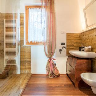 Modelo de cuarto de baño con ducha, tradicional, con armarios tipo mueble, puertas de armario de madera oscura, ducha empotrada, bidé, baldosas y/o azulejos beige, baldosas y/o azulejos marrones, paredes blancas, suelo de madera en tonos medios, lavabo sobreencimera, encimera de zinc, suelo marrón y ducha abierta
