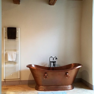 This is an example of a mediterranean bathroom in Other with a freestanding bath, white walls, terracotta flooring and beige floors.