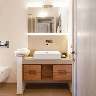 Immagine di una stanza da bagno design con WC sospeso, pareti beige e lavabo a bacinella