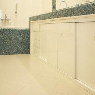 Exempel på ett mellanstort klassiskt turkos turkost badrum för barn, med släta luckor, vita skåp, ett platsbyggt badkar, en vägghängd toalettstol, vit kakel, porslinskakel, vita väggar, klinkergolv i porslin, ett nedsänkt handfat, kaklad bänkskiva och beiget golv