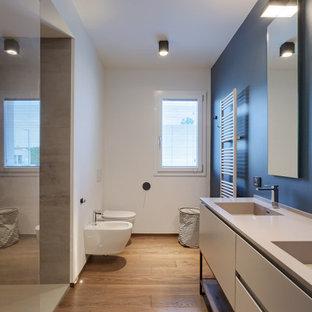 Inspiration för ett stort funkis grå grått badrum med dusch, med möbel-liknande, grå skåp, en dusch i en alkov, en vägghängd toalettstol, vita väggar, mellanmörkt trägolv, ett integrerad handfat och beiget golv