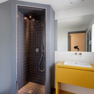 Imagen de cuarto de baño con ducha, contemporáneo, de tamaño medio, con armarios con paneles lisos, puertas de armario amarillas, ducha esquinera, baldosas y/o azulejos grises, baldosas y/o azulejos de porcelana, paredes blancas, lavabo encastrado, ducha abierta y encimeras amarillas
