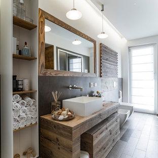 Inspiration för maritima brunt badrum med dusch, med skåp i mörkt trä, grå kakel, ett fristående handfat, träbänkskiva, en bidé och vita väggar