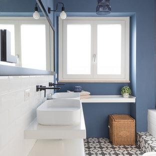Modern inredning av ett vit vitt badrum, med släta luckor, vita skåp, en bidé, vit kakel, tunnelbanekakel, blå väggar, ett fristående handfat och flerfärgat golv