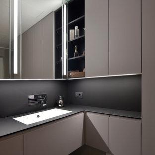 Immagine di una stanza da bagno minimal con ante lisce, ante grigie, lavabo sottopiano e top nero