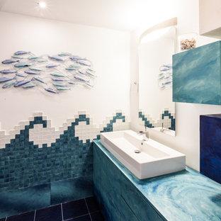Idee per una stanza da bagno con doccia contemporanea con ante lisce, ante turchesi, WC sospeso, piastrelle blu, piastrelle di vetro, pareti multicolore, pavimento con piastrelle in ceramica, lavabo rettangolare, pavimento blu e porta doccia scorrevole