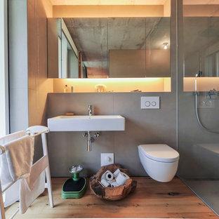 На фото: ванная комната среднего размера в современном стиле с душем без бортиков, инсталляцией, серой плиткой, паркетным полом среднего тона, душевой кабиной, подвесной раковиной и серыми стенами