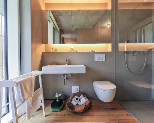 Mittelgroßes Modernes Duschbad Mit Bodengleicher Dusche, Wandtoilette,  Grauen Fliesen, Braunem Holzboden, Wandwaschbecken