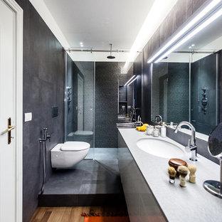 Ispirazione per una piccola stanza da bagno con doccia contemporanea con ante lisce, doccia ad angolo, piastrelle grigie, piastrelle nere, pareti grigie, pavimento in legno massello medio, lavabo integrato, top in marmo e porta doccia scorrevole