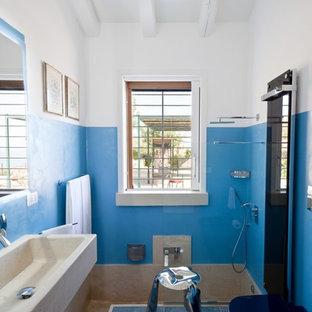 Cette image montre une salle de bain principale méditerranéenne avec une baignoire en alcôve, un combiné douche/baignoire, un mur bleu, une grande vasque et aucune cabine.