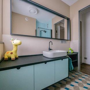 Idee per una piccola stanza da bagno per bambini contemporanea con ante lisce, piastrelle beige, piastrelle in gres porcellanato, pareti beige, pavimento in cementine, lavabo a bacinella, top in superficie solida, pavimento multicolore, top nero e ante blu