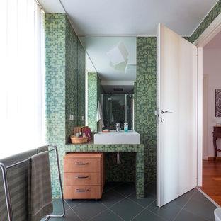 Ejemplo de cuarto de baño principal, actual, pequeño, con armarios con paneles lisos, puertas de armario de madera clara, ducha empotrada, sanitario de dos piezas, baldosas y/o azulejos verdes, baldosas y/o azulejos en mosaico, paredes verdes, suelo de baldosas de cerámica, lavabo de seno grande, encimera de azulejos, suelo verde, ducha con puerta con bisagras y encimeras verdes