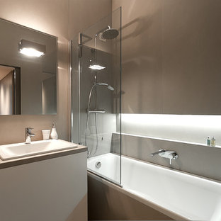 Idee per una stanza da bagno con doccia contemporanea con ante lisce, ante grigie, vasca ad angolo, vasca/doccia, pareti grigie, lavabo da incasso, top in superficie solida e doccia aperta