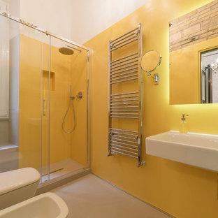 Immagine di una stanza da bagno con doccia eclettica con doccia alcova, WC sospeso, pareti gialle, pavimento in cemento, lavabo sospeso, pavimento beige e porta doccia scorrevole