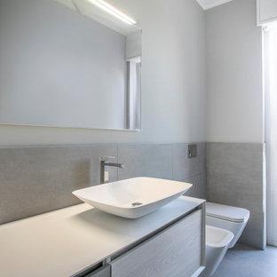 Réalisation d'une salle de bain design de taille moyenne avec un placard à porte affleurante, des portes de placard en bois clair, un WC suspendu, un carrelage gris, des carreaux de porcelaine, un mur gris, un sol en bois peint, une vasque, un plan de toilette en surface solide, un sol beige, une cabine de douche à porte battante et un plan de toilette blanc.