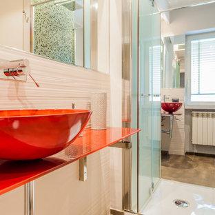 Diseño de cuarto de baño con ducha, minimalista, pequeño, con armarios con paneles lisos, puertas de armario blancas, ducha abierta, sanitario de pared, baldosas y/o azulejos beige, baldosas y/o azulejos de porcelana, paredes beige, suelo de baldosas de porcelana, lavabo sobreencimera, encimera de vidrio, suelo gris, ducha con puerta con bisagras y encimeras rojas