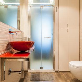 Diseño de cuarto de baño con ducha, moderno, pequeño, con armarios con paneles lisos, puertas de armario blancas, ducha abierta, sanitario de pared, baldosas y/o azulejos beige, baldosas y/o azulejos de porcelana, paredes beige, suelo de baldosas de porcelana, lavabo sobreencimera, encimera de vidrio, suelo gris, ducha con puerta con bisagras y encimeras rojas