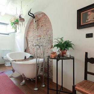 Ispirazione per una stanza da bagno padronale mediterranea con vasca con piedi a zampa di leone, WC a due pezzi, doccia alcova, pareti beige, parquet scuro e pavimento marrone