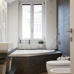 Exempel på ett litet modernt en-suite badrum, med öppna hyllor, ett hörnbadkar, en dusch/badkar-kombination, en bidé, vita väggar, ett fristående handfat, brunt golv, grå kakel, ljust trägolv och med dusch som är öppen