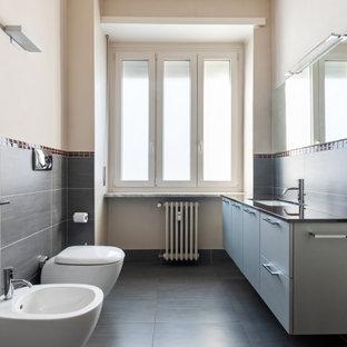 Foto di una stanza da bagno con doccia minimal di medie dimensioni con ante lisce, ante grigie, WC sospeso, piastrelle nere, piastrelle in gres porcellanato, pareti beige, pavimento in gres porcellanato, lavabo sottopiano, pavimento nero e top nero