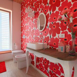 Esempio di una stanza da bagno con doccia bohémian di medie dimensioni con consolle stile comò, bidè, pareti rosse, pavimento in legno massello medio, lavabo a bacinella, top in legno, pavimento beige e top marrone